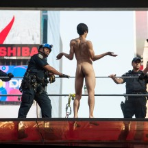 NYPD trying to remove naked man atop TKTS Booth in Times Square, just before jumping, missing NYPD airbag and injuring himself.