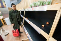 Shopper at Trader Joe's next to empty produce shelves, as throngs of people shop for groceries on eve of predicted giant snowstorm, NYC