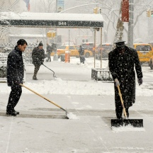 Various men shoveling snow on Fifth Ave between 76th and 75th streets, NYC