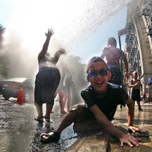 Children cooling off in spray of fire hydrant, Washington Heights, NYC
