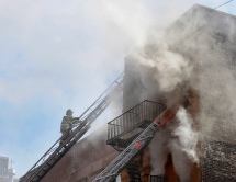 Firefighter climbing ladder at scene of building fire, West 115th Street, Between Frederick Douglas Blvd and Adam Clayton Powell Blvd, NYC.