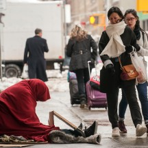 People walking past homeless man sitting on sidewalk on Seventh Ave between 50th and 51st Streets, NYC.