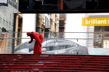 Worker cleaning glass, appearing to be washing car on billboard. Times Square, NYC.