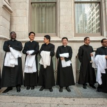 Scenes from the St. Patrick's Day Parade, Fifth Ave, NYC. Group of priests outside St. Patrick's cathedral after mass.