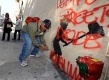 Richard Santiago AKA 'Apollo', an old-school NYC graffiti artist, removing plexiglass cover on Banksy painting, West 79th Street @ Broadway, NYC.