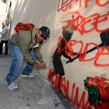 Richard Santiago AKA 'Apollo', an old-school NYC graffiti artist, removing plexiglass cover on Banksy painting, West 79th Street @ Broadway, NYC.