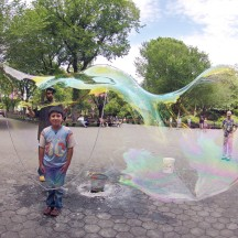 Young boy looking inside giant soap bubble, Central Park, NYC.