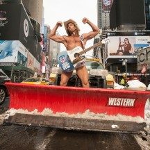 The Naked Cowboy on snow plow truck in middle of Times Square, West 45th, NYC.