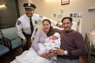 122618-CHRISTMAS-BABY-DM-10 Proud parents holding newborn baby in Bellevue Hospital after father, along with two NYPD officers, delivered baby at the Queens Midtown Tunnel plaza last night. Here: Lieutenant Harry Persad, Maria Albarracin 36, Ivan Albarracin 39, baby: Alie Aurora Albarracin. David McGlynn 12/26/18